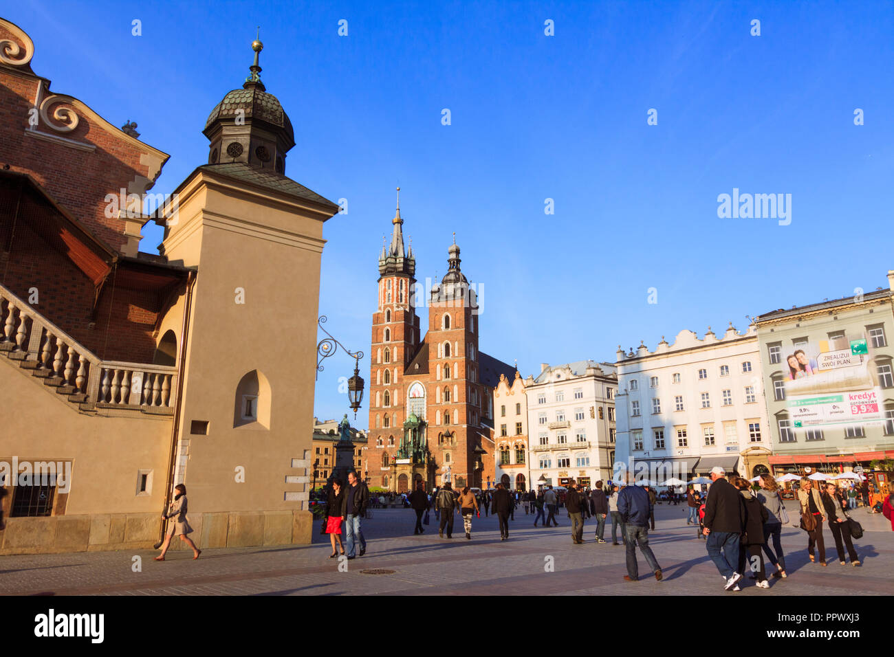 Krakow, Poland : People walk past the Cloth Hall and St. Mary's Basilica Church of Our Lady Assumed into Heaven a 14th century Brick Gothic church at  - Stock Image