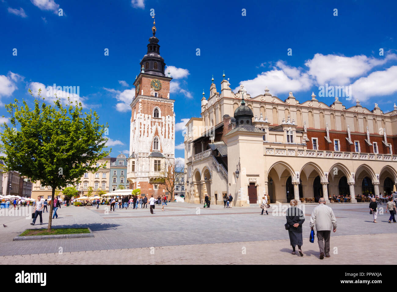 Krakow, Poland : People walks towards the Cloth hall building and old Town Hall Tower at the center of the main market square in the Krakow Old Town ( Stock Photo