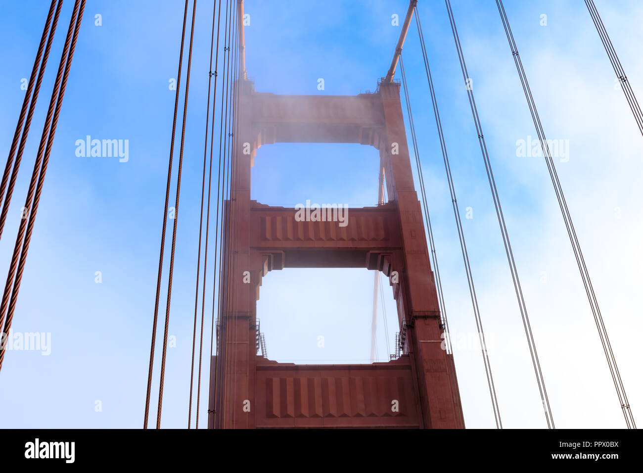 Fog rolling in on the Golden Gate Bridge tower. - Stock Image