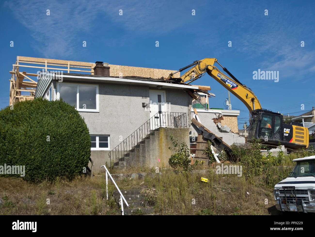 A 1950s bungalow being demolished in a Metro Vancouver suburb, with another home under construction next door. - Stock Image