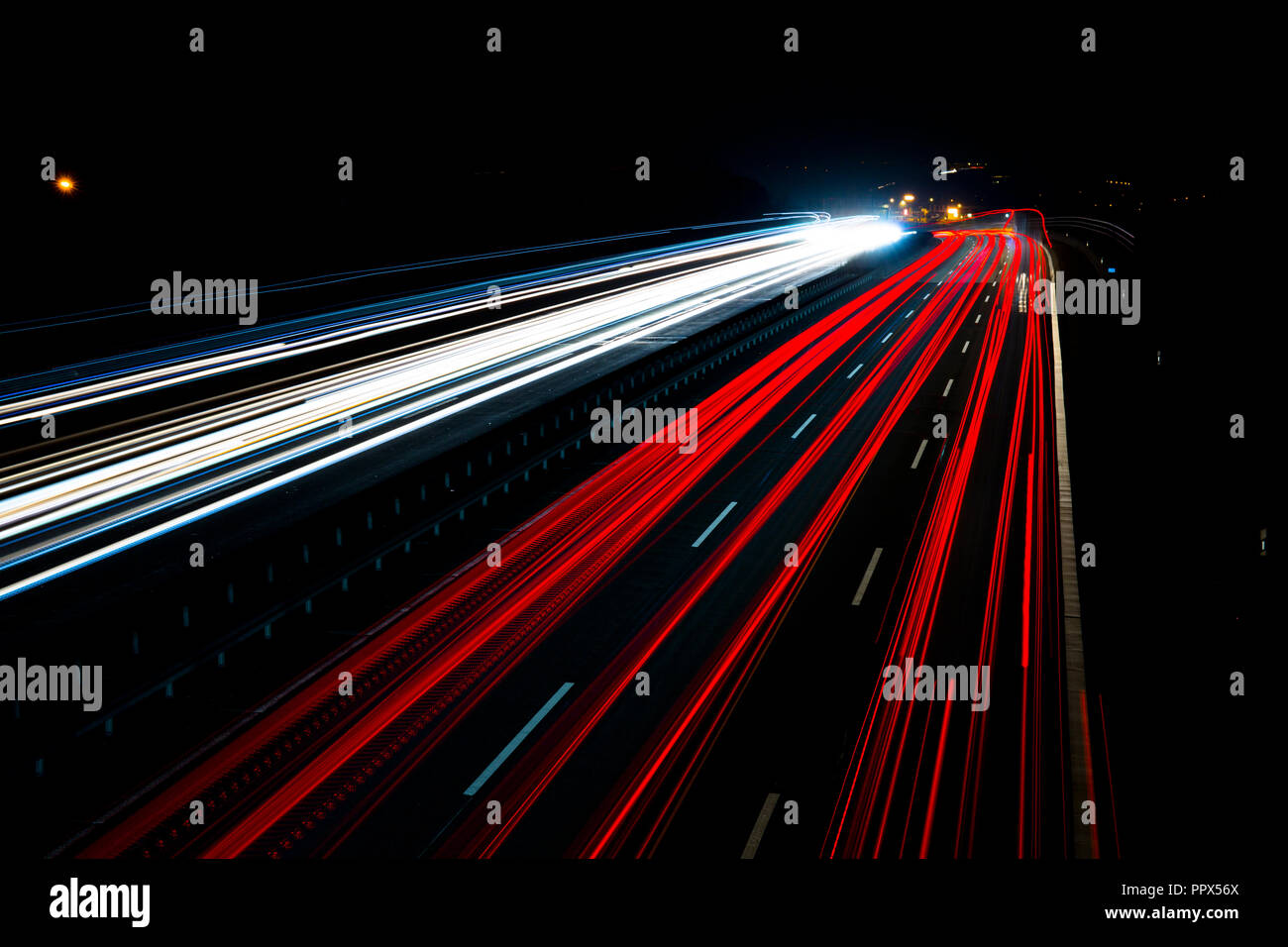 Night traffic trails on a german highway, motion blur, with trucks, cars and busses, in Germany, Autobahn 3 - Stock Image