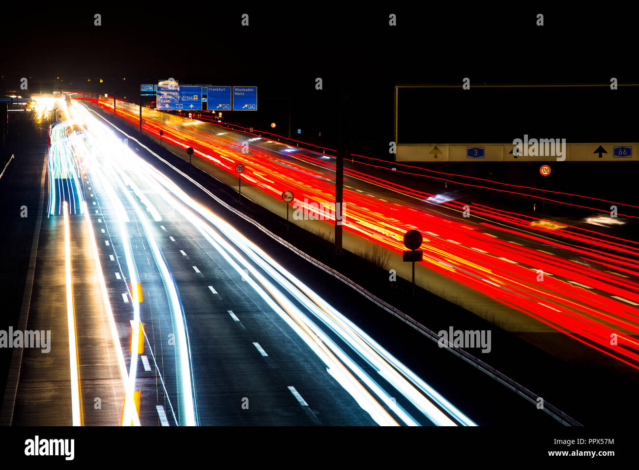 Night traffic trails on a german highway, motion blur, with trucks, cars and busses, in Germany, A3, Wiesbadener Kreuz - Stock Image