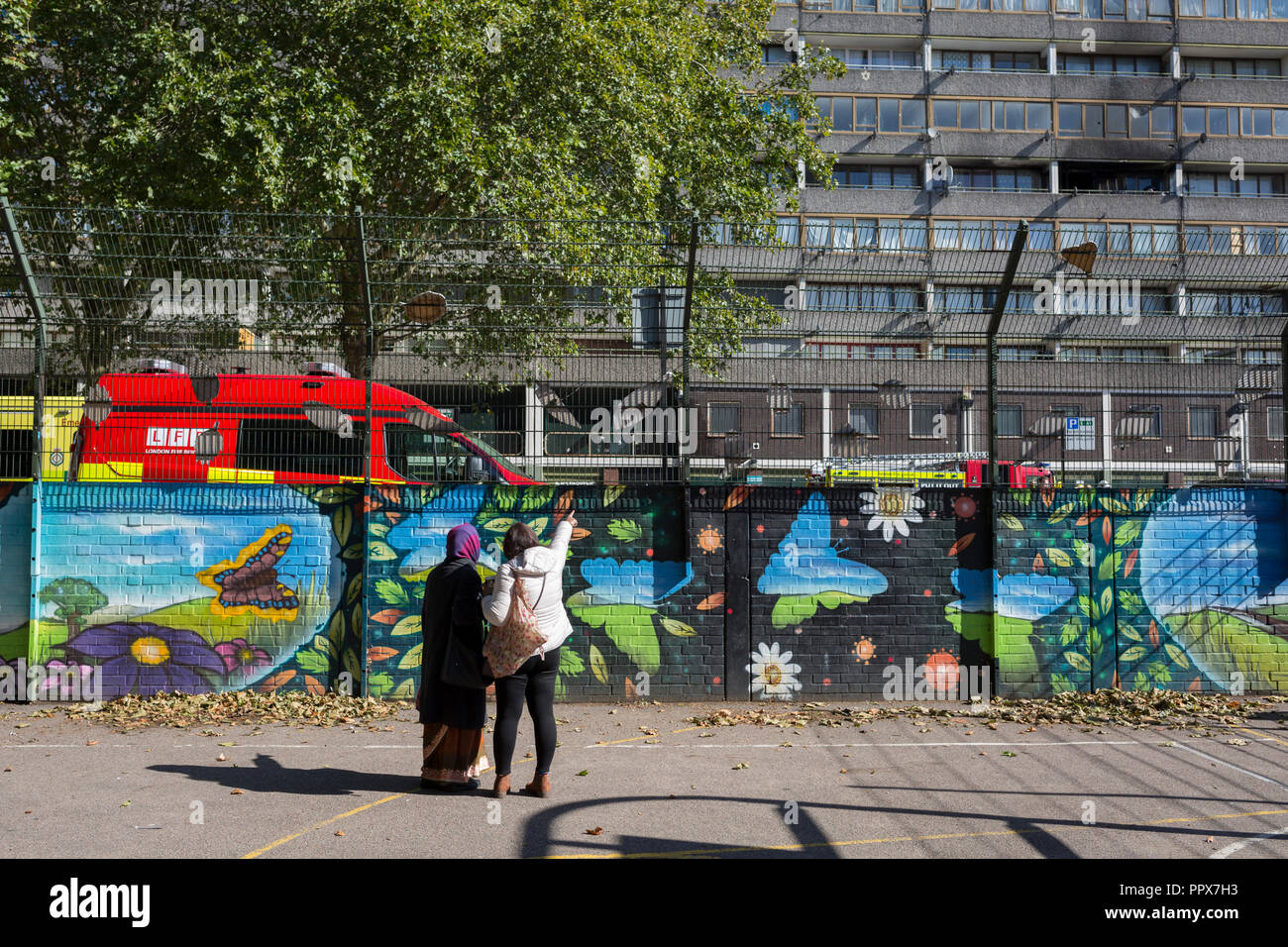 Local estate residents look up at smoke damage aftermath on the exterior of a flat fire in one of the two Wendover blocks on Alsace Road in the Aylesbury Estate, Southwark SE17, on 24th September 2018, in London, England. Part of a split level flat on the fourth and fifth floor of the 15-storey block was damaged. One woman and two children left the property before the Brigade arrived. They were treated at the scene for smoke inhalation by London Ambulance Service crews and taken too hospital. Another man was also treated at the scene for smoke inhalation. - Stock Image