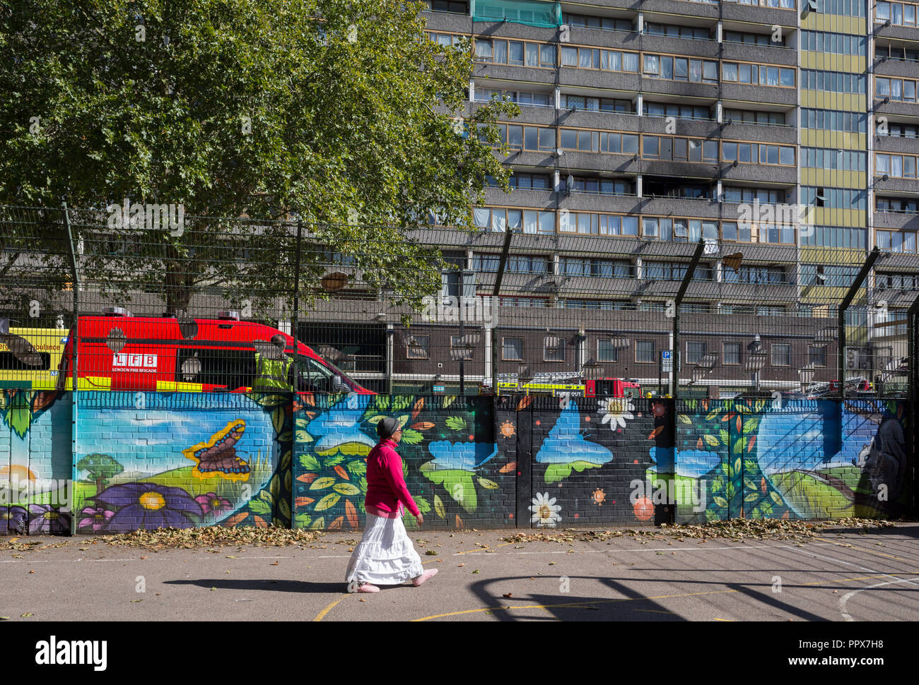 A local estate resident walks past smoke damage aftermath on the exterior of a flat fire in one of the two Wendover blocks in Alsace Road on the Aylesbury Estate, Southwark SE17, on 24th September 2018, in London, England. Part of a split level flat on the fourth and fifth floor of the 15-storey block was damaged. One woman and two children left the property before the Brigade arrived. They were treated at the scene for smoke inhalation by London Ambulance Service crews and taken too hospital. Another man was also treated at the scene for smoke inhalation. - Stock Image