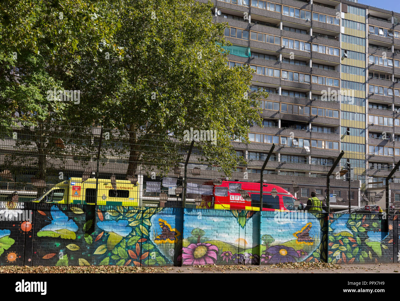 Emergency Services vehicles are parked by a basketball court in the aftermath of a flat fire in one of the two Wendover blocks in Alsace Road on the Aylesbury Estate, Southwark SE17, on 24th September 2018, in London, England. Part of a split level flat on the fourth and fifth floor of the 15-storey block was damaged. One woman and two children left the property before the Brigade arrived. They were treated at the scene for smoke inhalation by London Ambulance Service crews and taken too hospital. Another man was also treated at the scene for smoke inhalation. - Stock Image