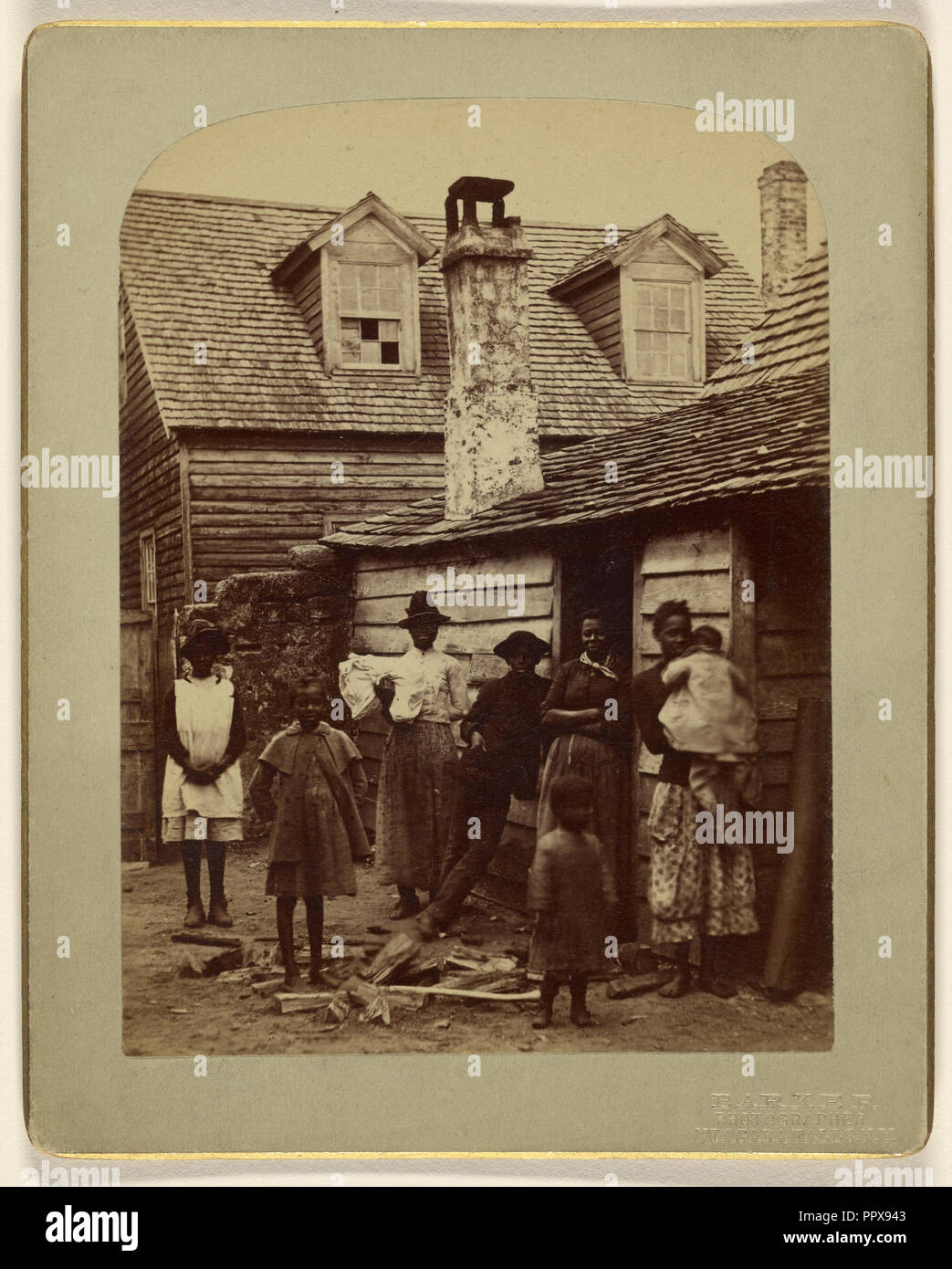 Black family grouping of eight posed at house entrance; George Barker, American, 1844 - 1894, 1886; Albumen silver print - Stock Image