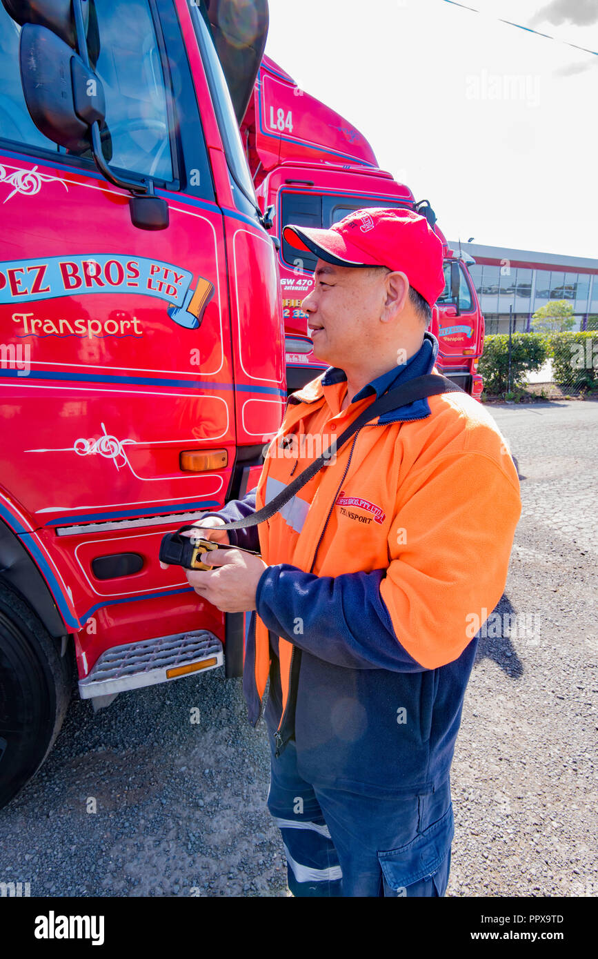 An Vietnamese born truck driver uses a remote device to operate machinery on the back of a large truck in Sydney Australia - Stock Image