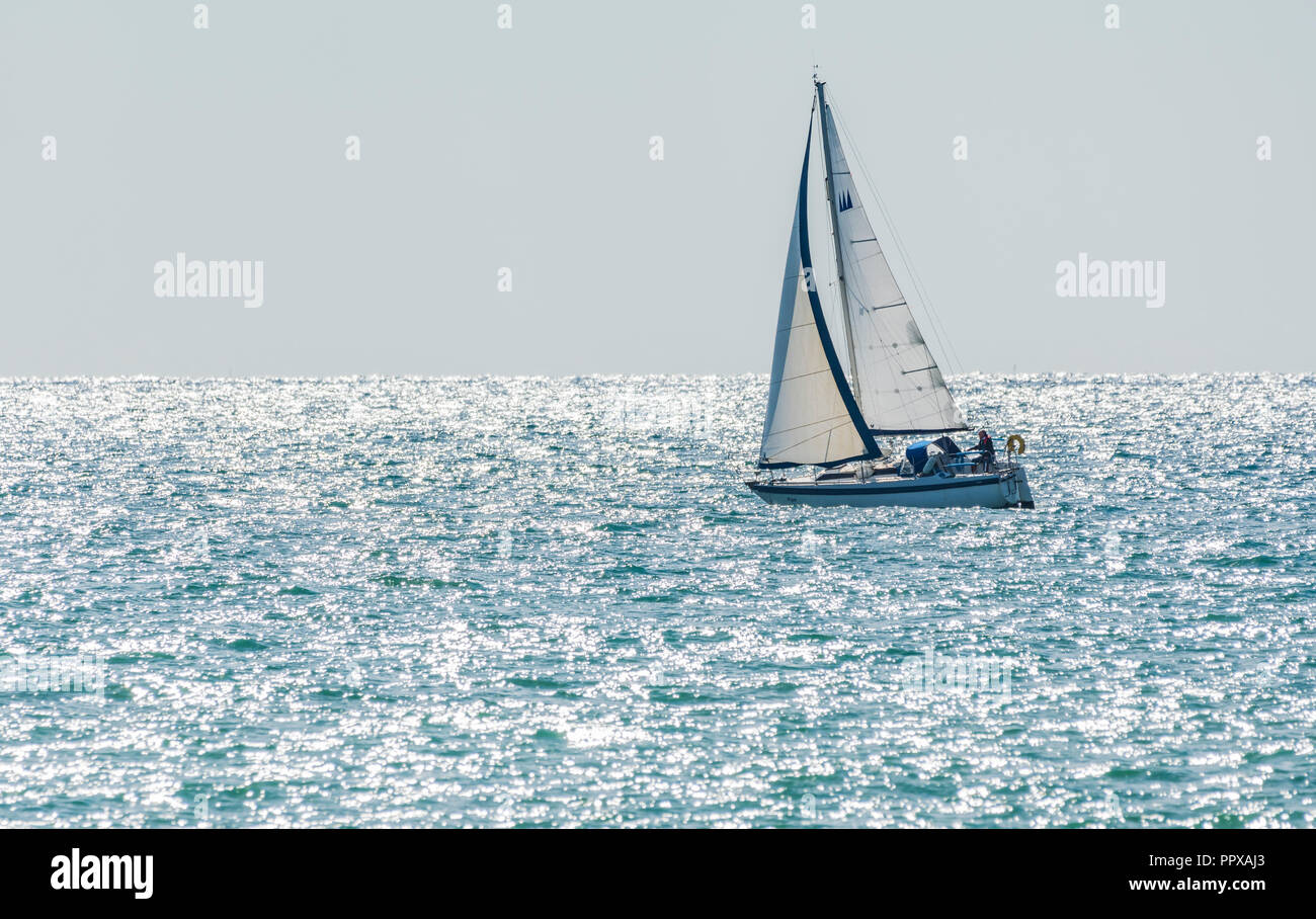 Single person yacht sailing at sea with the morning sun sparkling in the ocean, in the UK. - Stock Image