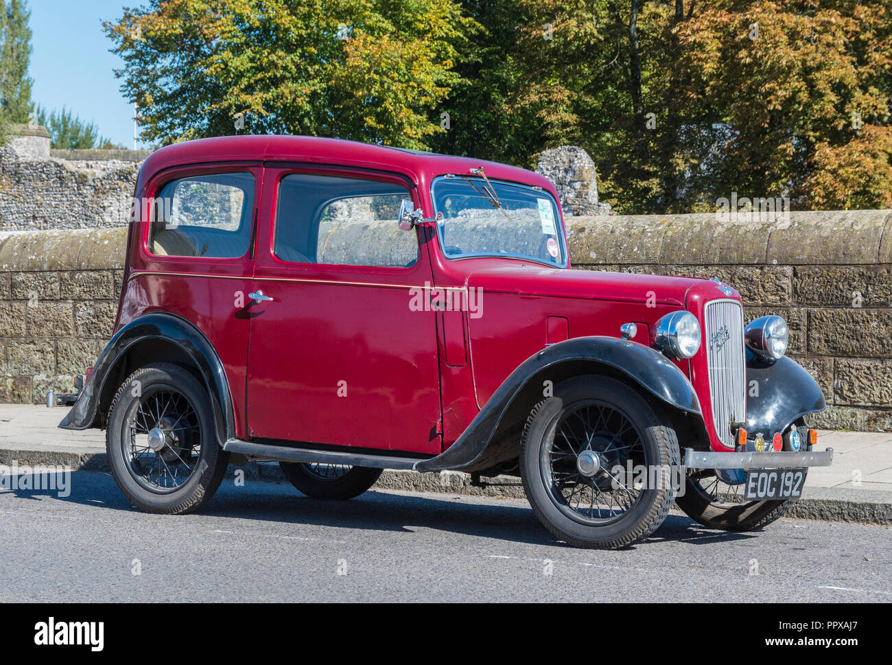 Red Austin Seven (Austin 7) vintage saloon car from 1938 parked by the roadside in the UK. Stock Photo
