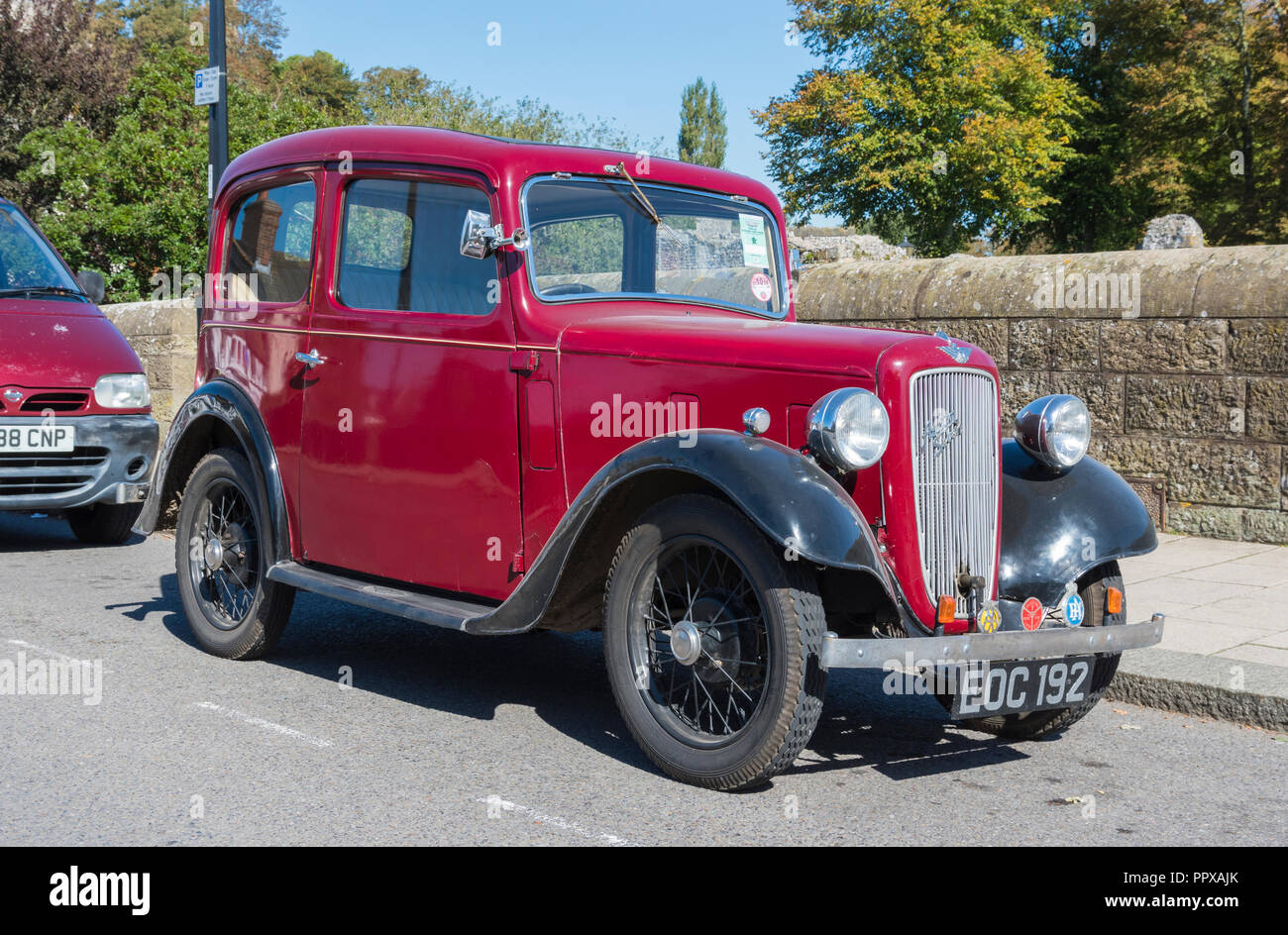 Red Austin Seven (Austin 7) vintage saloon car from 1938 parked by the roadside in the UK. - Stock Image