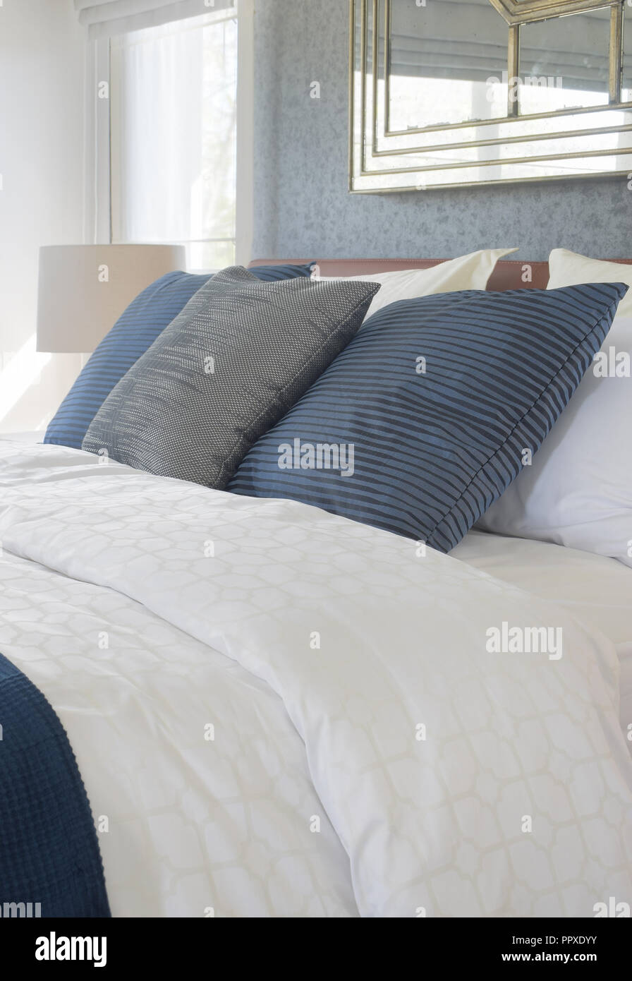 Dark color scheme pillows on bed with comfy bedding - Stock Image