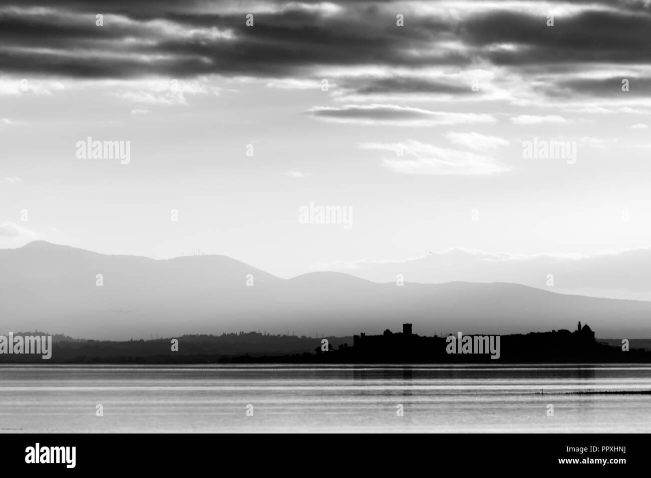 Beautiful view of Trasimeno lake at sunset Castiglione del Lago town in the background Stock Photo