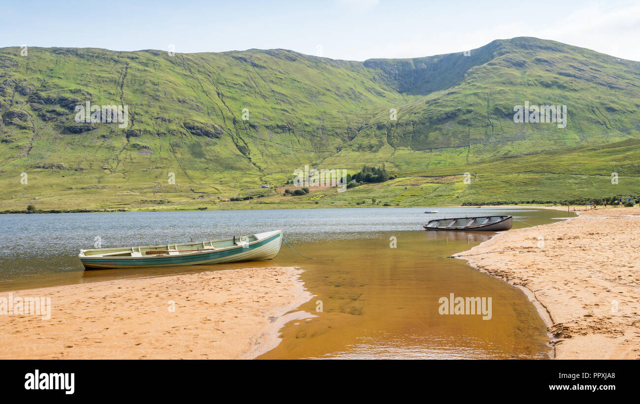 Boats on the beach at scenic Lake Nafooey in County Galway in Ireland. Stock Photo