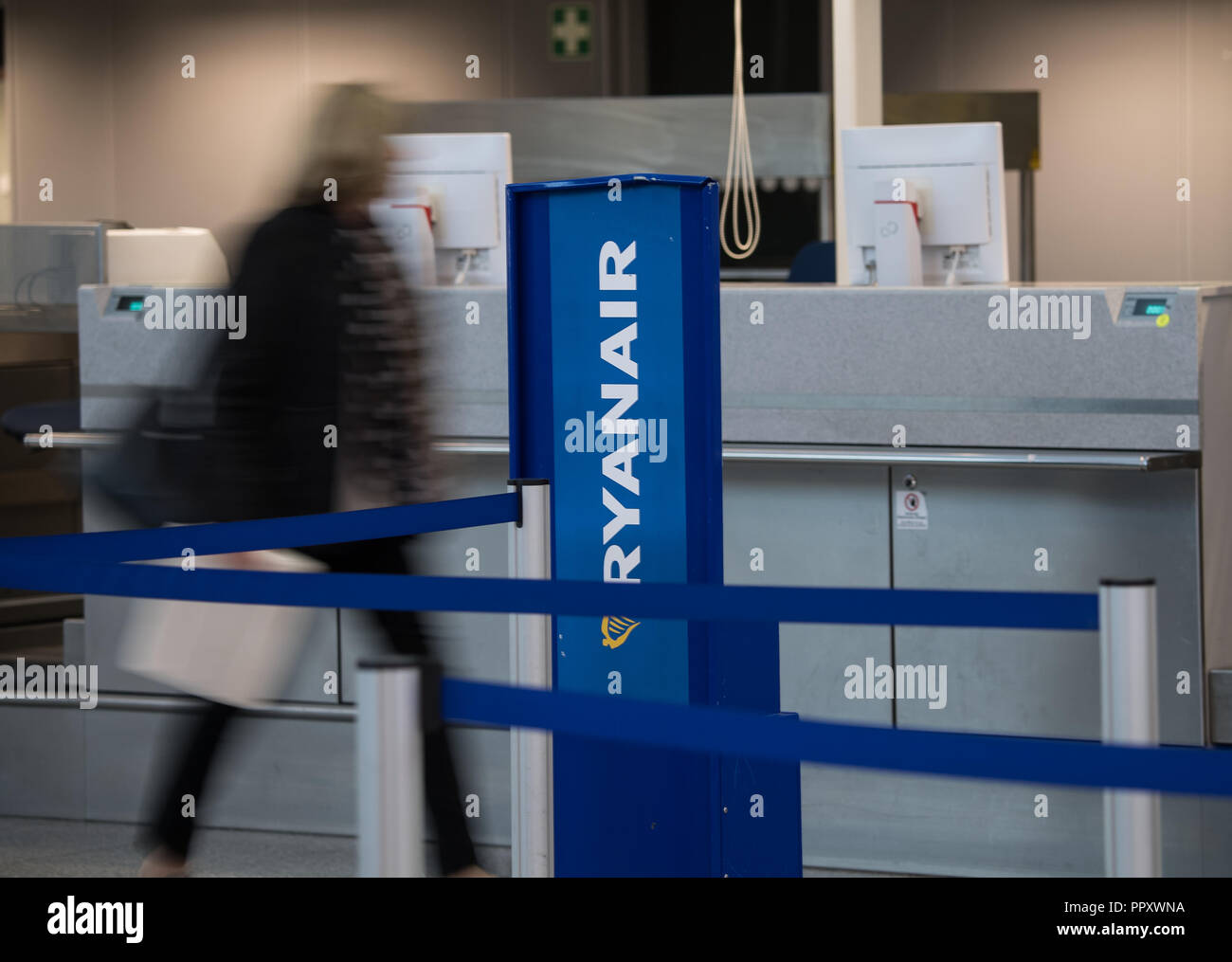 28 September 2018, Hessen, Frankfurt_Main: A woman walks past the Ryanair counter at the airport. Trade unions in several European countries have called for strikes at low-cost airline Ryanair. In Germany, the pilots of the Cockpit Association (VC) and the flight attendants organized at Verdi participate. Photo: Andreas Arnold/dpa - Stock Image
