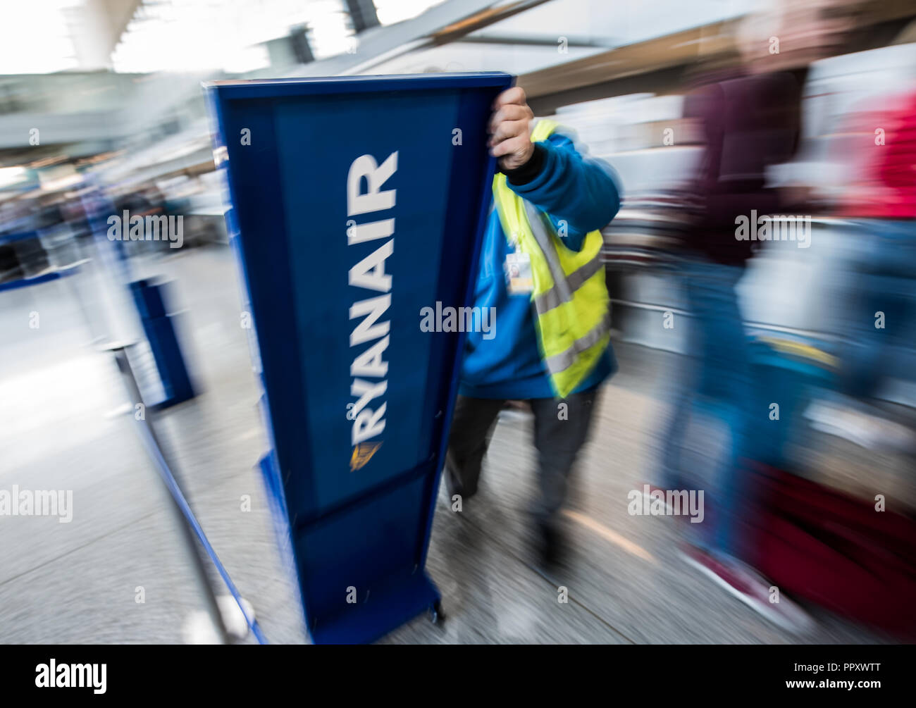 28 September 2018, Hessen, Frankfurt_Main: An airport employee moves a Ryanair display. Trade unions in several European countries have called for strikes at low-cost airline Ryanair. In Germany, the pilots of the Cockpit Association (VC) and the flight attendants organized at Verdi participate. Photo: Andreas Arnold/dpa - Stock Image