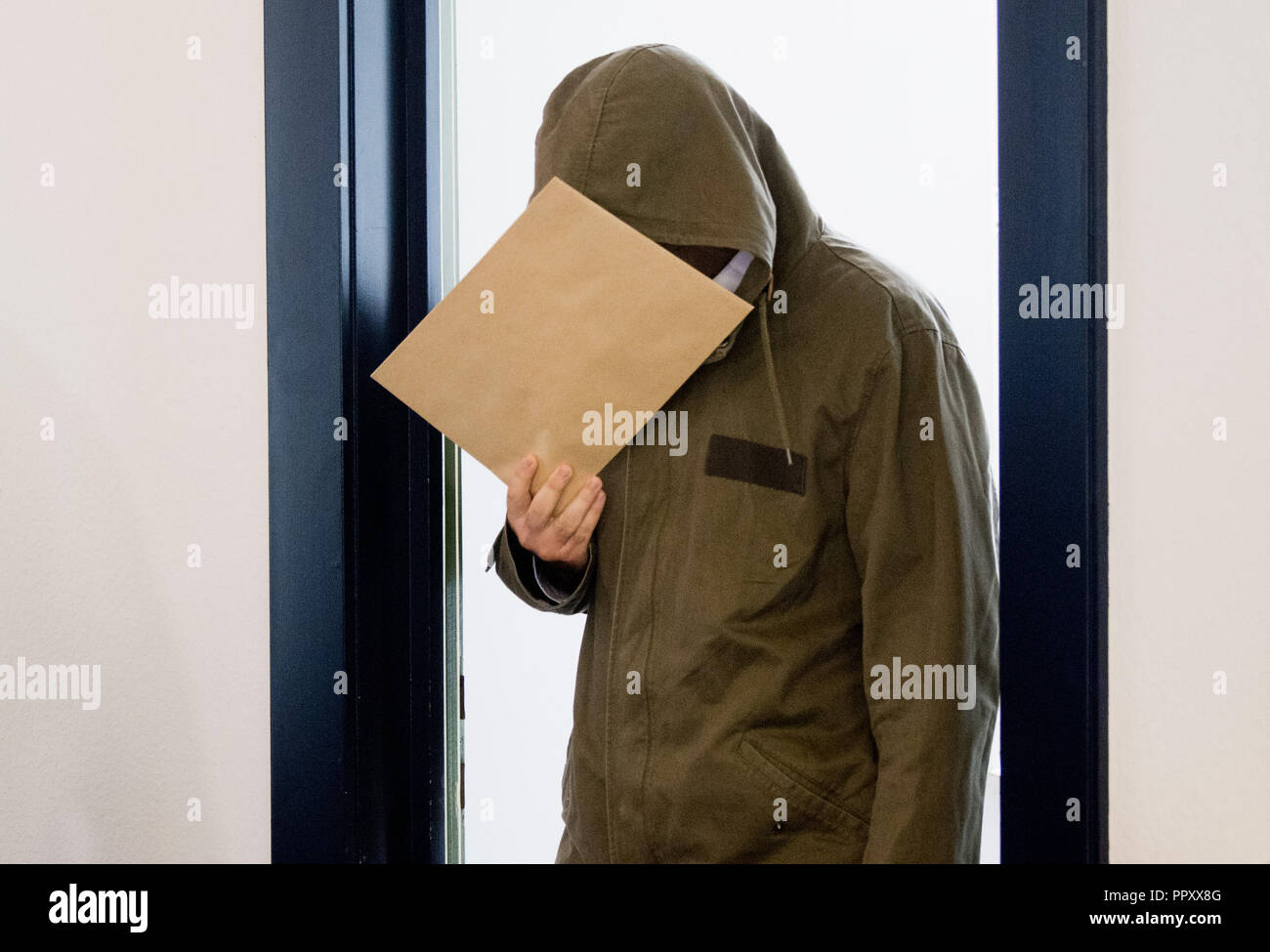28 September 2018, Lower Saxony, Celle: One of the two defendants enters a room of the district court. Because it allegedly supported the terrorist militia Islamic State IS and called for attacks, a pair of twins from Salzgitter have to answer to the Higher Regional Court in Celle. The trial shall take place on the premises of the Local Court. Photo: Julian Stratenschulte/dpa - Stock Image