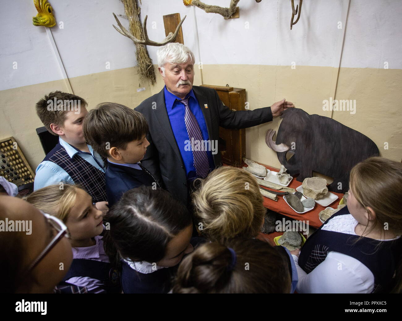 Russia. 27th Sep, 2018. OMSK REGION, RUSSIA - SEPTEMBER 27, 2018: History and social studies teacher Yakov Savenok, 65, with students in a local history museum in the village of Bogoslovka. Dmitry Feoktistov/TASS Credit: ITAR-TASS News Agency/Alamy Live News - Stock Image