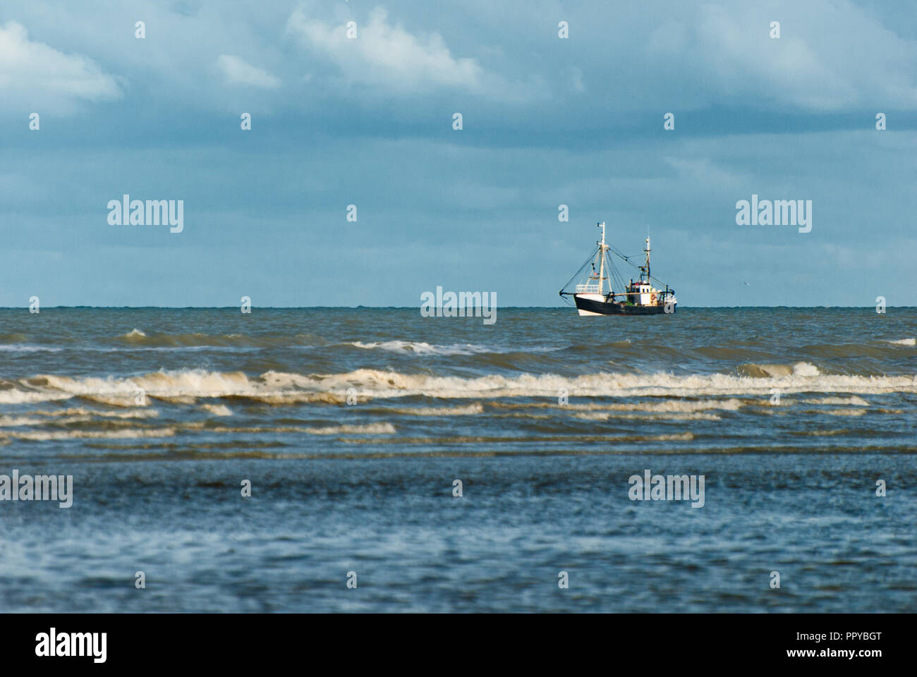 fishing boat fishing at evening near the coast in autumn - Stock Image