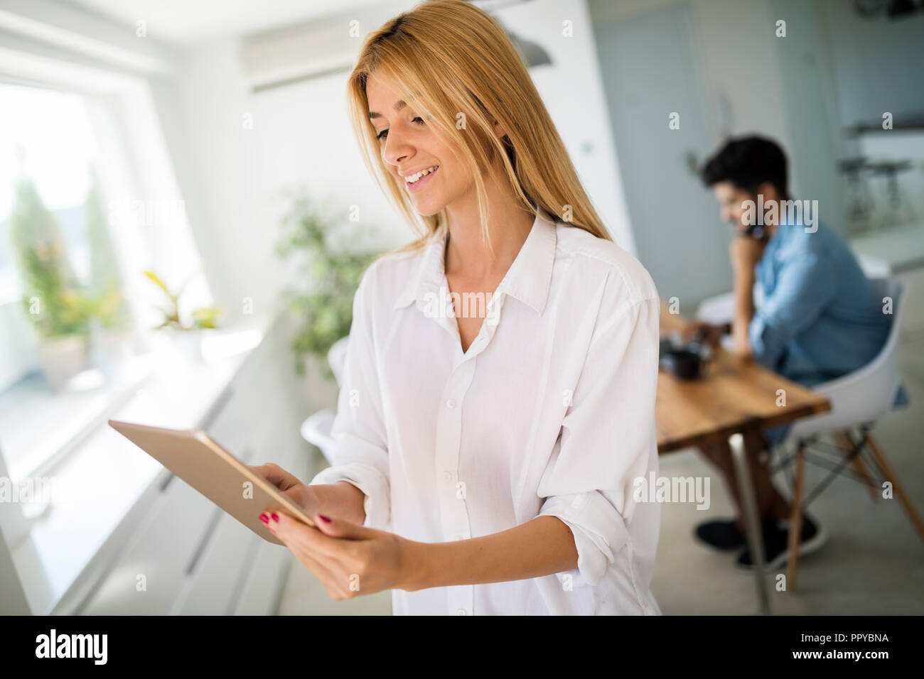 Attractive woman working on a tablet in a home office. Stock Photo