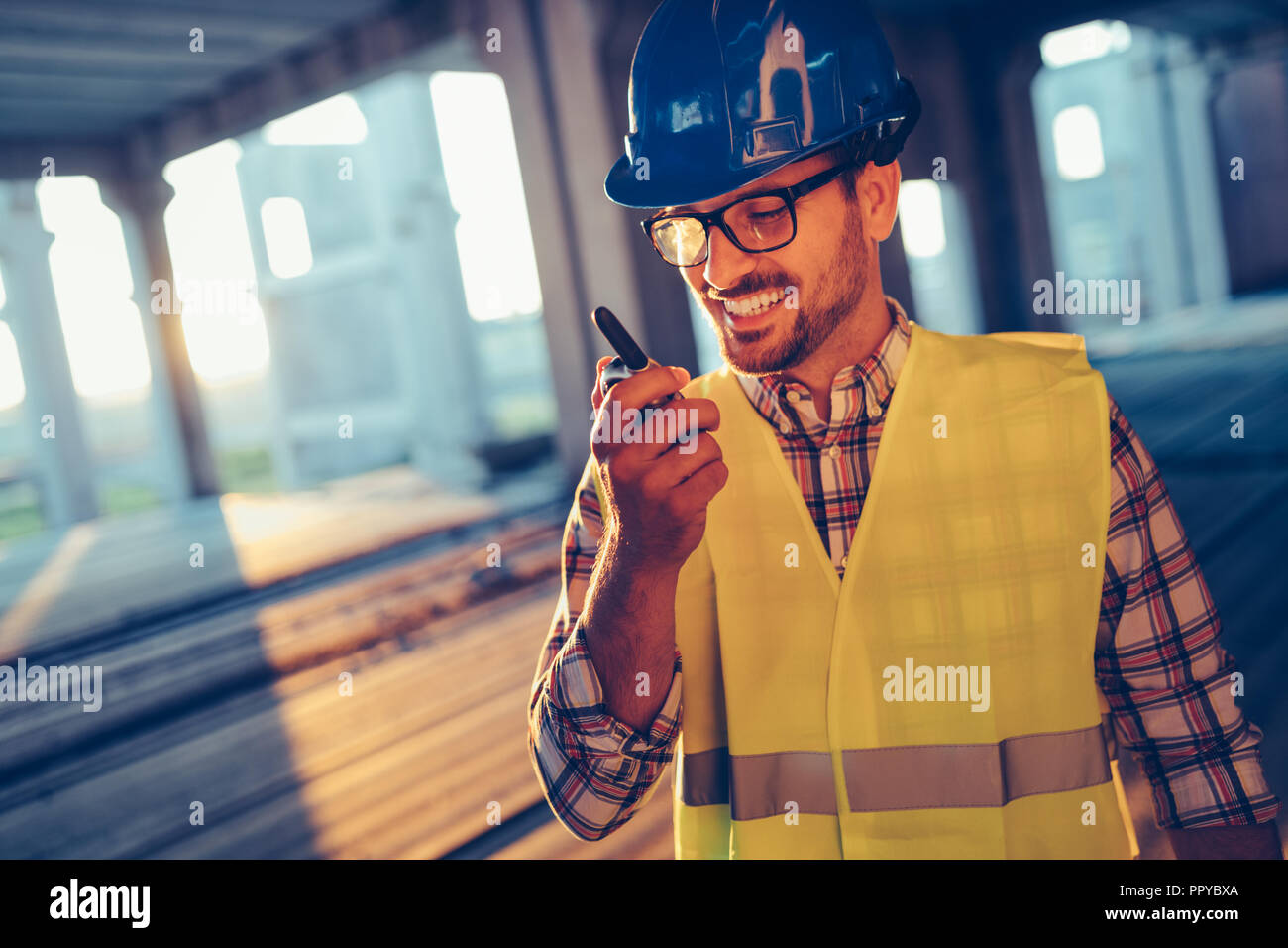 Male architect communicating on walkie-talkie at site - Stock Image