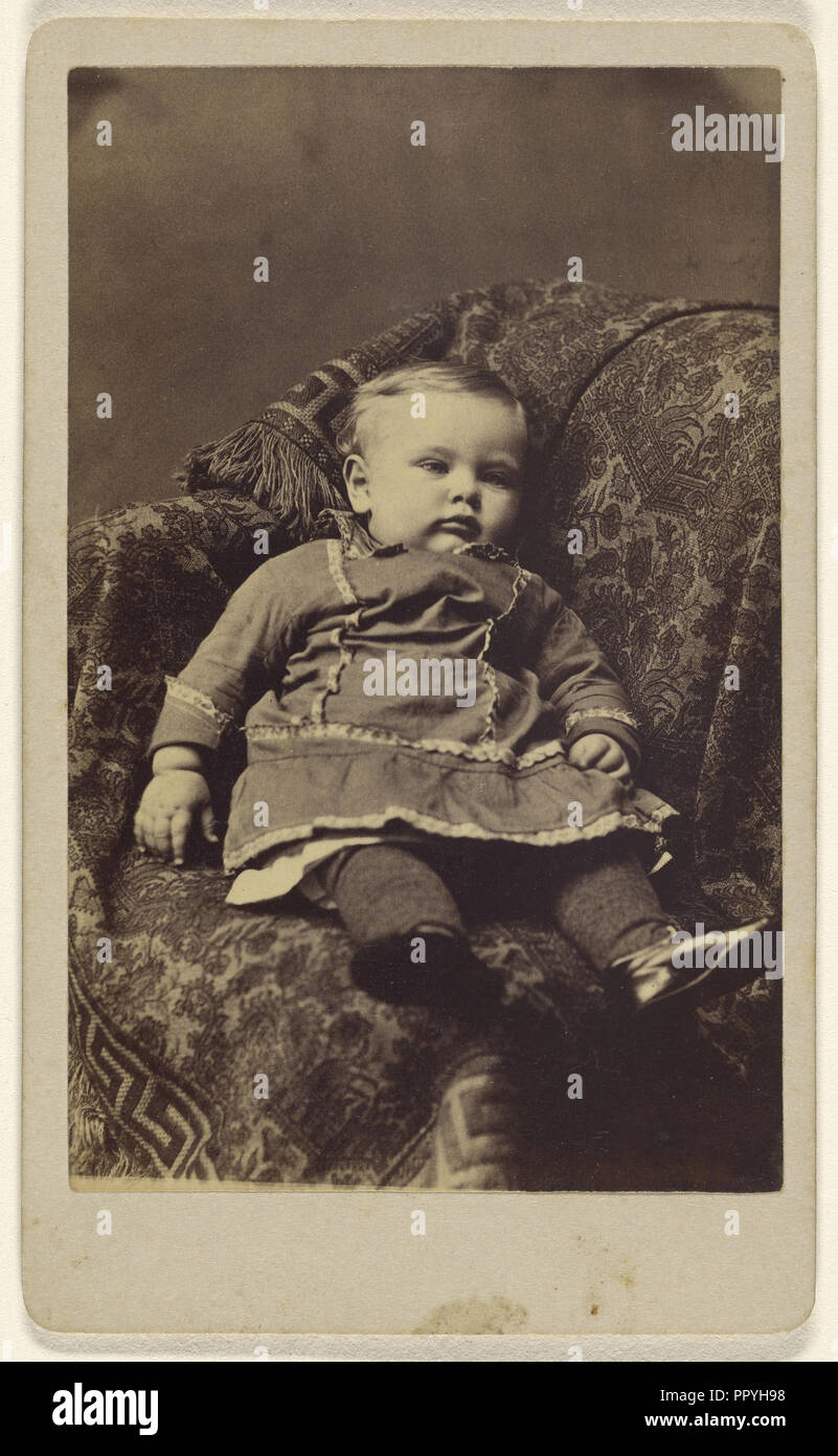 child seated in a large upholstered chair; Louis Hess, American, active Cobleskill, New York 1860s, 1870-1880; Albumen silver - Stock Image
