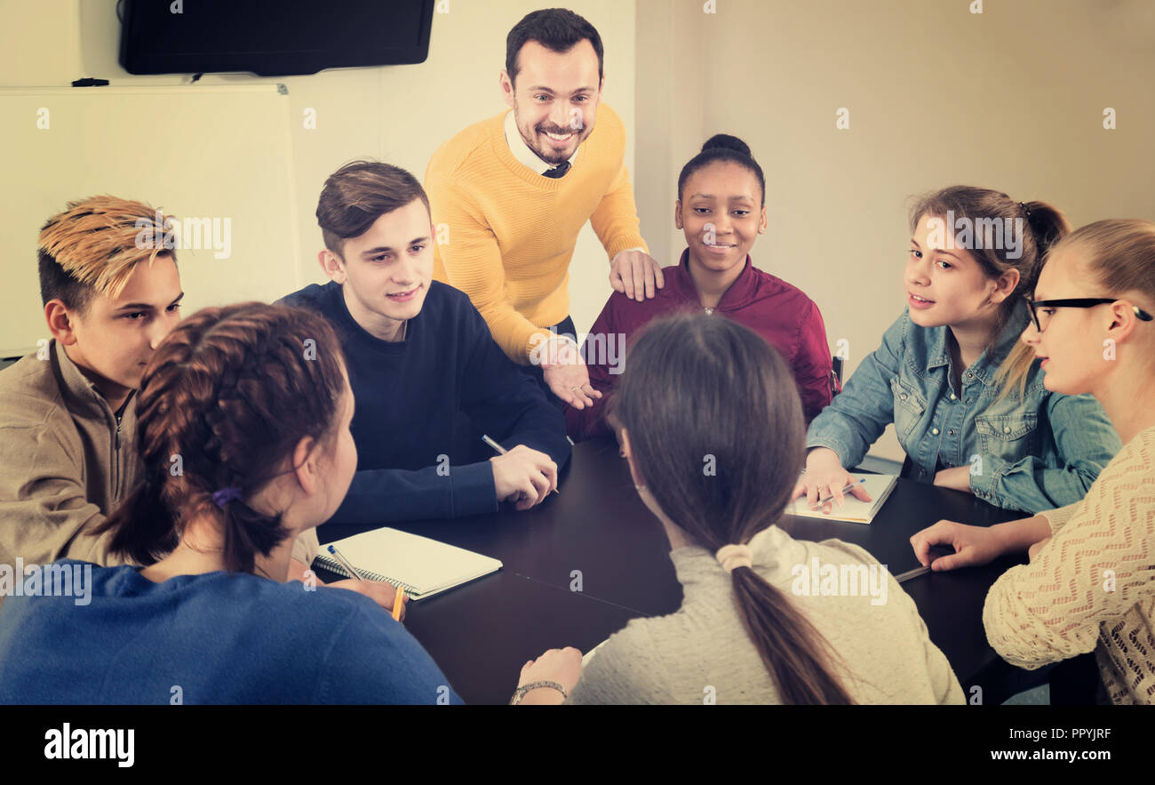 concentrated classmates having difficult project to complete during class sits by the table - Stock Image