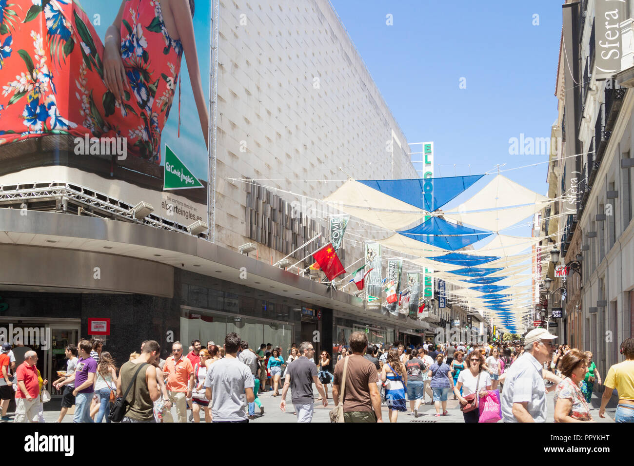 Shoppers outside El Corte Ingles department store in Madrid, Spain. Canopy over street to filter hot summer sun. - Stock Image