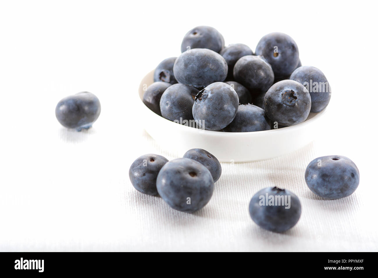 Close up of a white bowl with juicy blueberries on a white tablecloth with some blueberrie scattered on the table - Stock Image