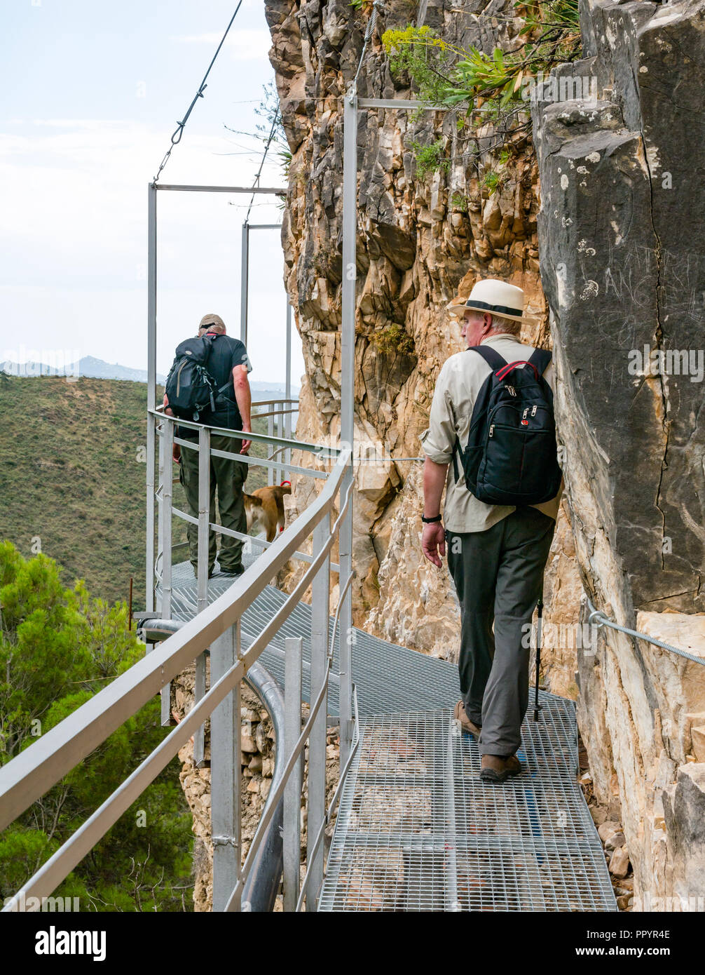 Older men walking on mountain gorge cliff metal walkway, Sierras de Tejeda Natural park, Axarquia, Andalusia, Spain - Stock Image