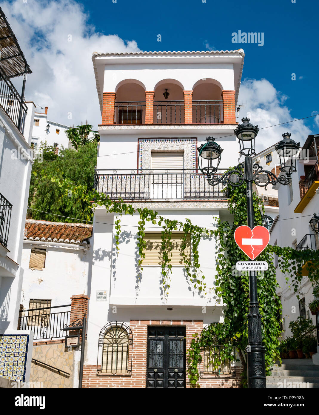 Pretty white houses with zero tolerance of domestic violence sign in Spanish, Canillas de Acientuna, Axarquia, Andalusia, Spain - Stock Image