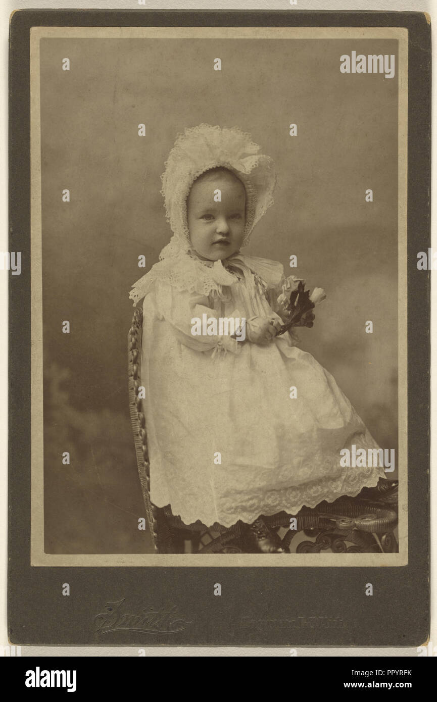 baby wearing a bonnet, holding a flower, seated  Smith, American, active  Burlington, Iowa 1870s, about 1890  Albumen silver e6b8f55b695