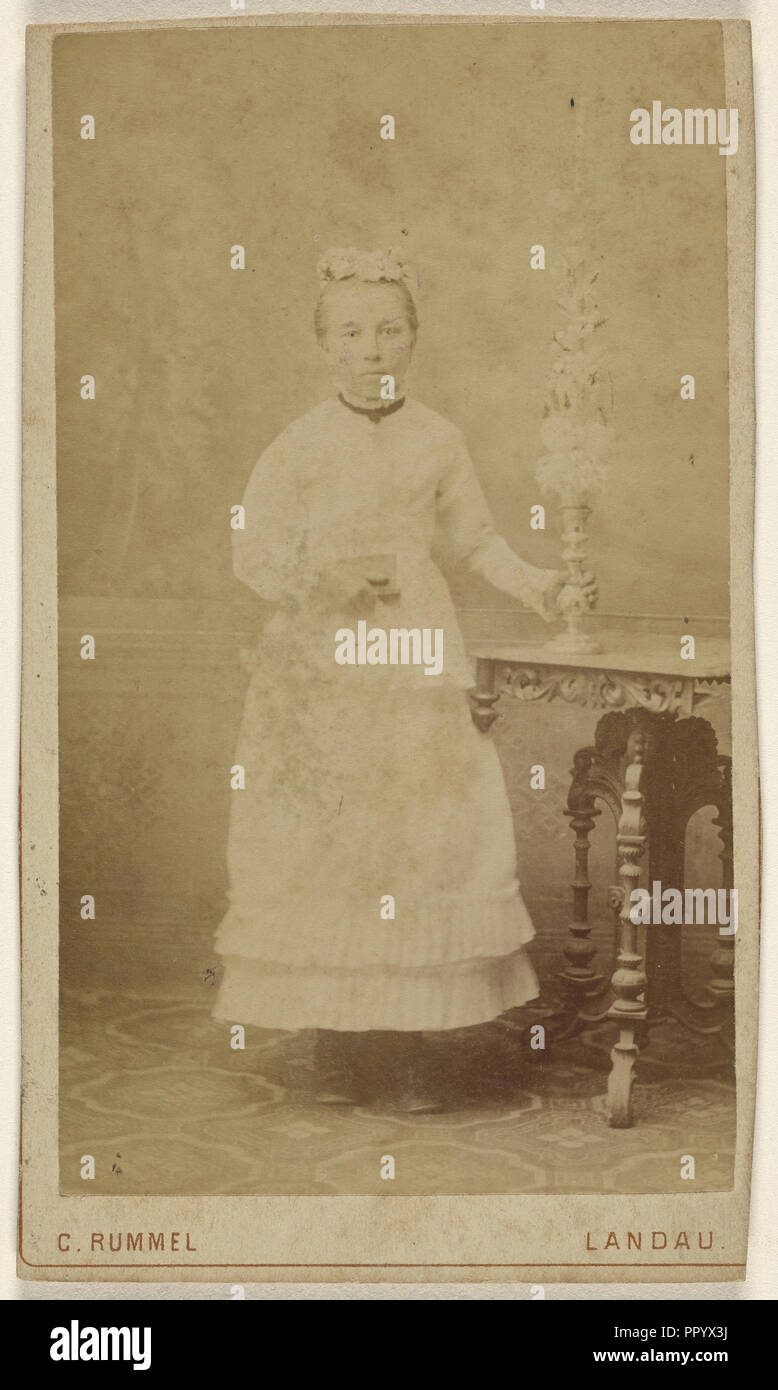 small woman standing, holding a vase on a table; C. Rummel, German, active Landau, Germany 1870s, 1870 - 1875; Albumen silver - Stock Image