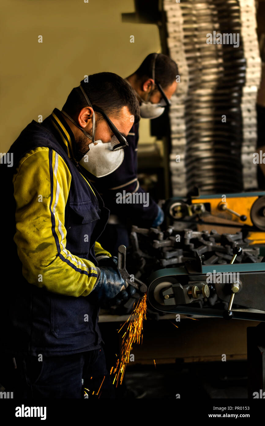 A worker grinding metal in metal and foundry factory. Stock Photo