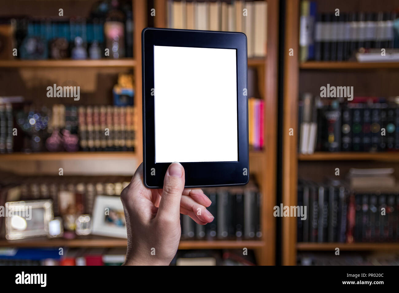 Womand hand holding e reader in front of bookshelves - Stock Image