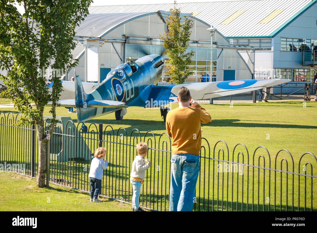 A man and his children watch as a Spitfire passes close by at Sywell aerodrome - Stock Image
