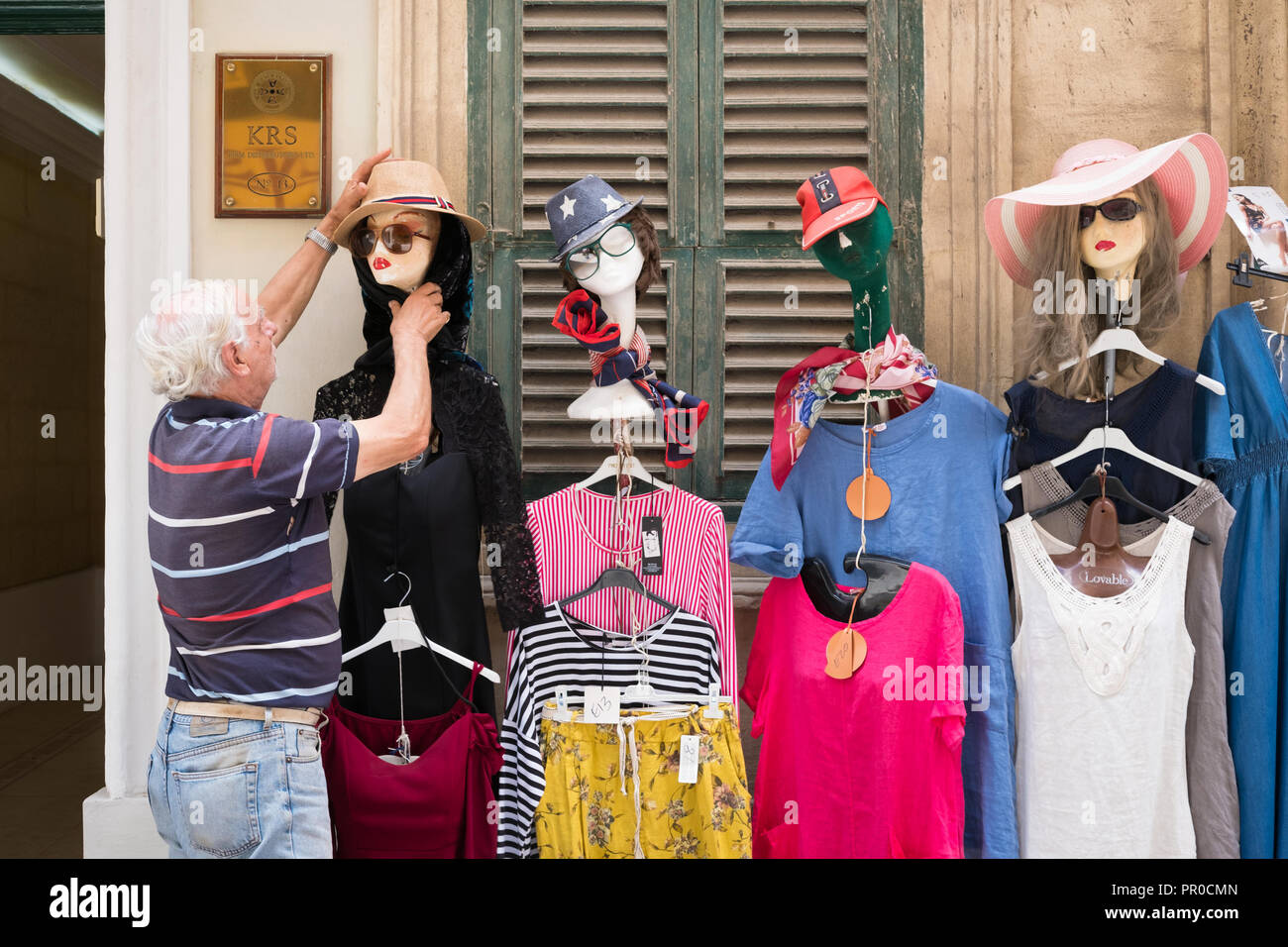 Maltese seller arranges clothes on a mannequin on the street in Valletta, Malta. - Stock Image