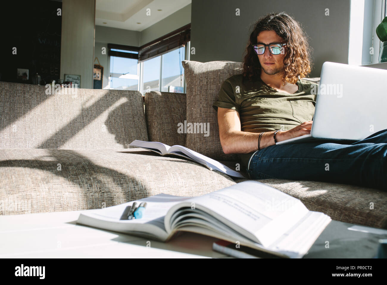 Young man studying for exams sitting on couch at home with sunlight coming from window. Student studying for exam on laptop with books in front. - Stock Image