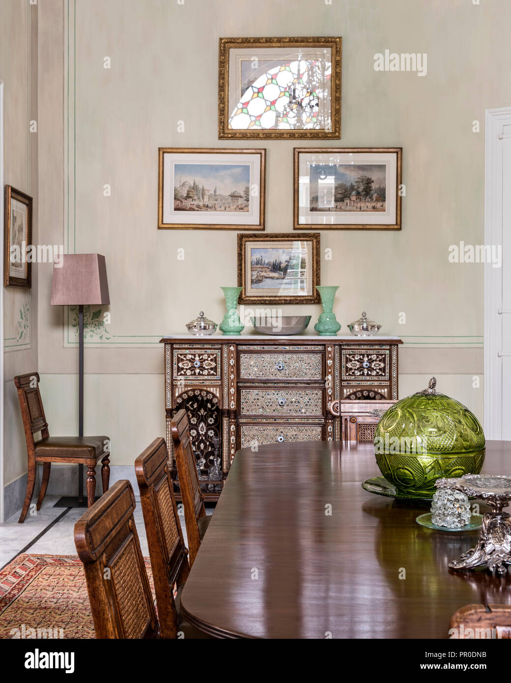 Antique dining table and 24 cane-backed chairs with inlaid Syrian chest dating from 1800's. Stock Photo