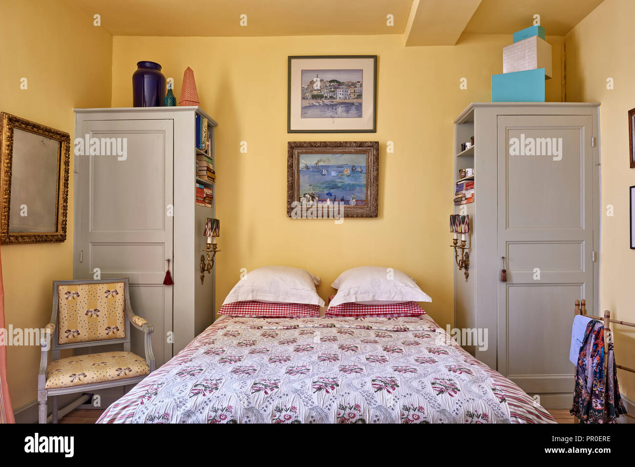 Framed artwork by Deliss family above double bed with built in cupboards - Stock Image