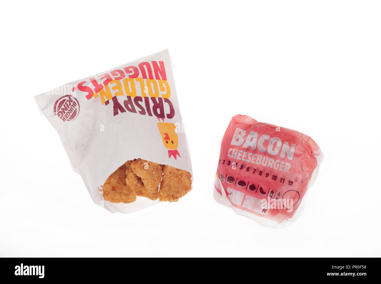 Burger King wrapped Bacon Cheeseburger and packet of chicken nuggets - Stock Image