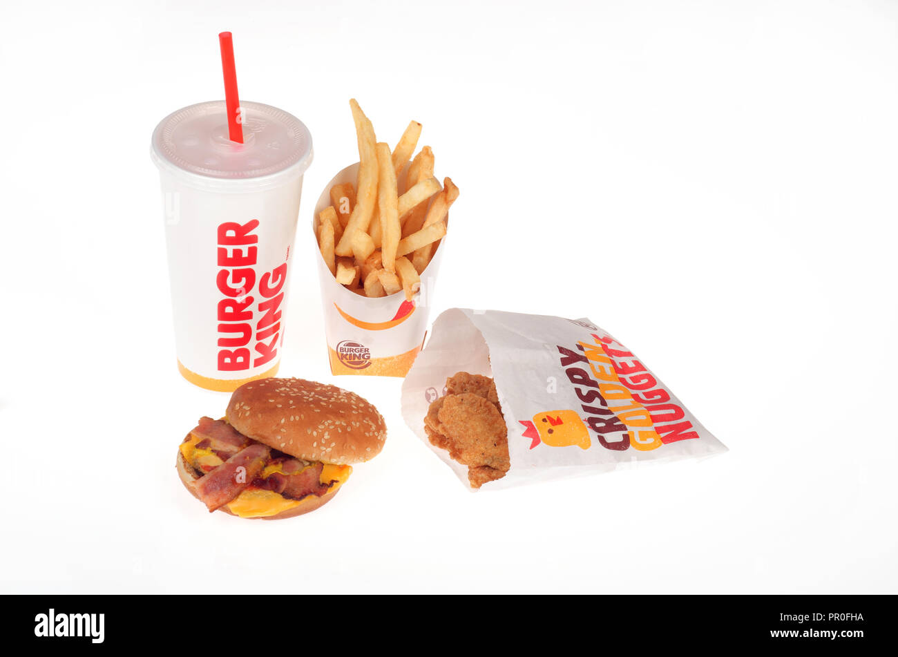 Burger King meal with a bacon cheeseburger, french fries, chicken nuggets and soda pop - Stock Image