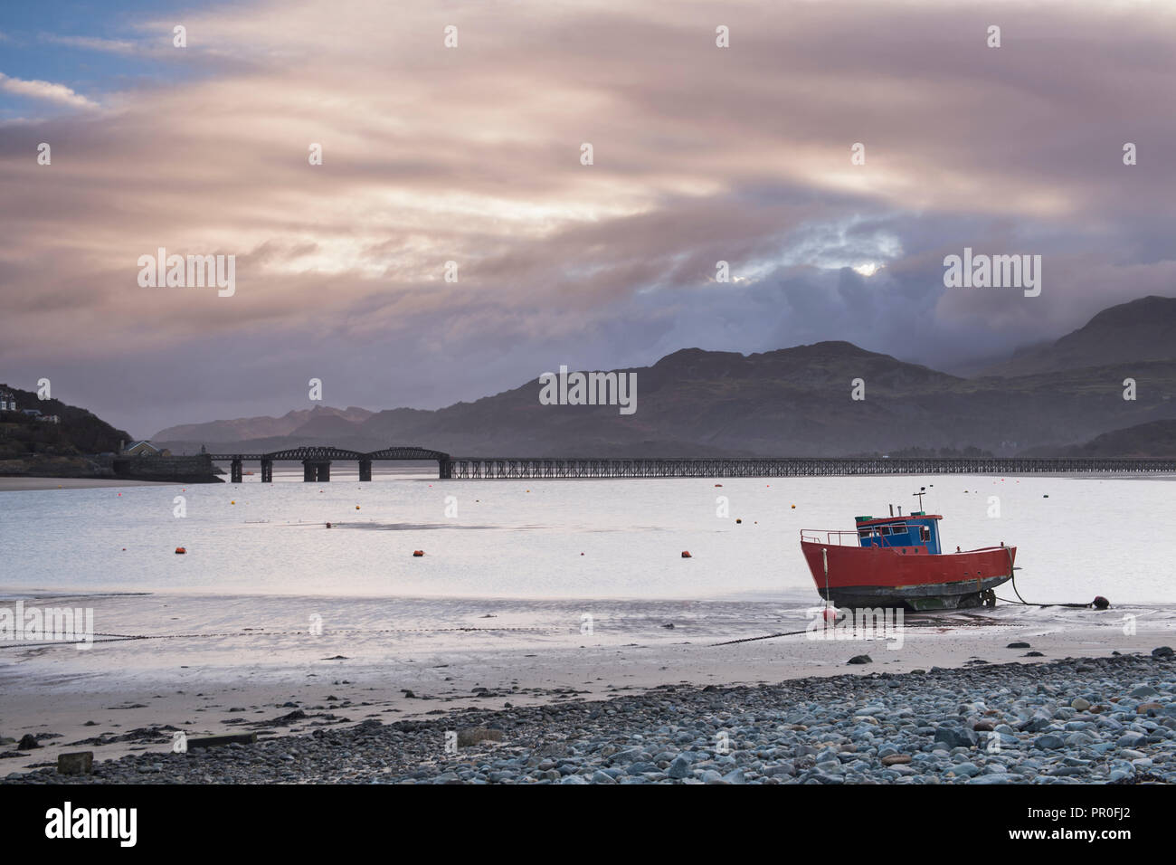 Fishing boat and Barmouth Bridge in Barmouth Harbour with Cader (Cadair) Mountains behind, Snowdonia National Park, North Wales, Wales, United Kingdom Stock Photo