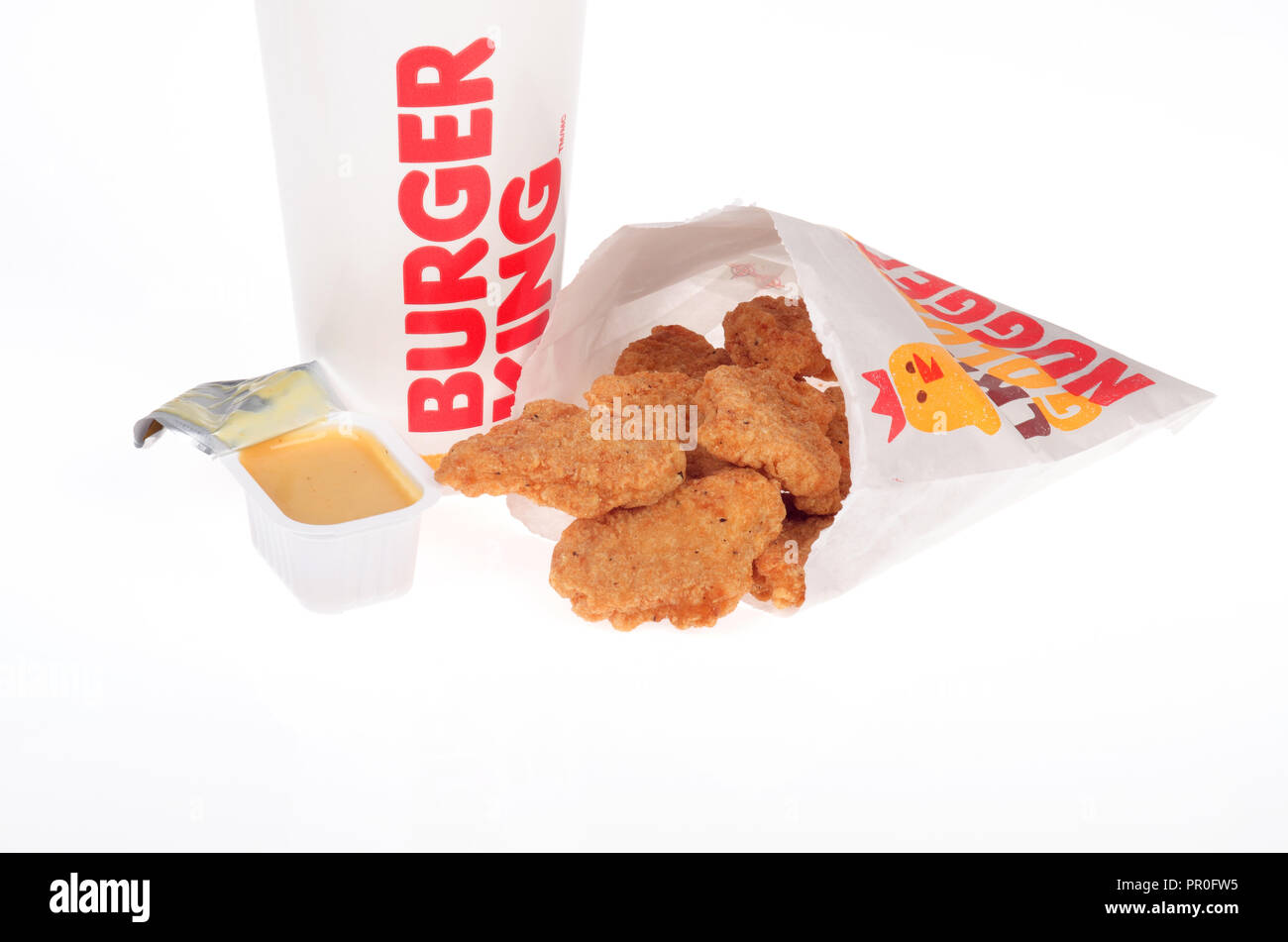 Burger King chicken nuggets with honey mustard dipping sauce and a drink cup - Stock Image