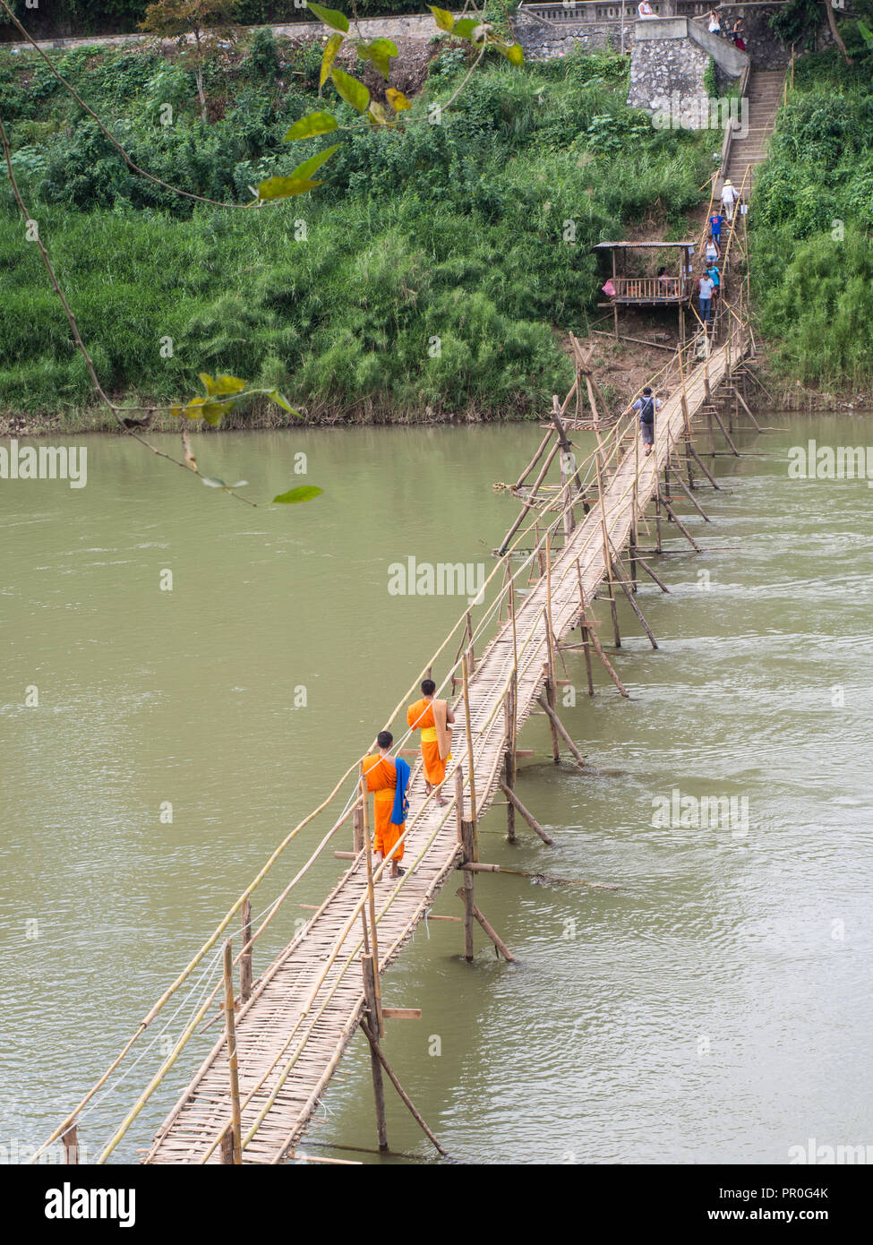 Orange-clad Buddhist monks crossing a bamboo bridge, Luang Prabang, Laos, Indochina, Southeast Asia, Asia - Stock Image
