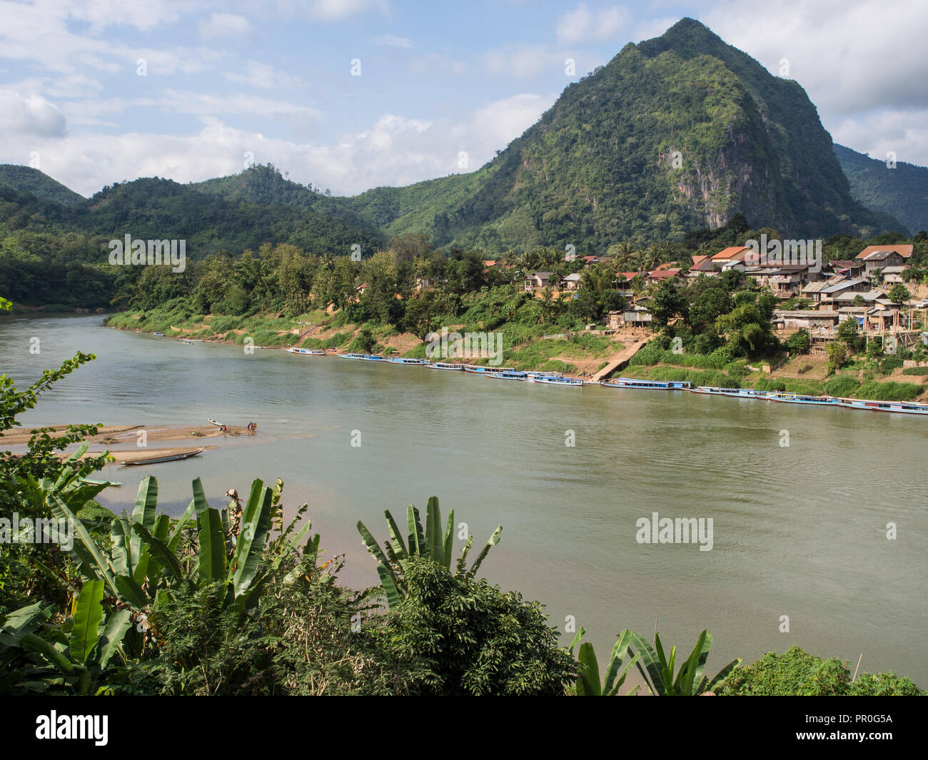 Village, river, and mountains, Nong Khiaw, Laos, Indochina, Southeast Asia, Asia - Stock Image