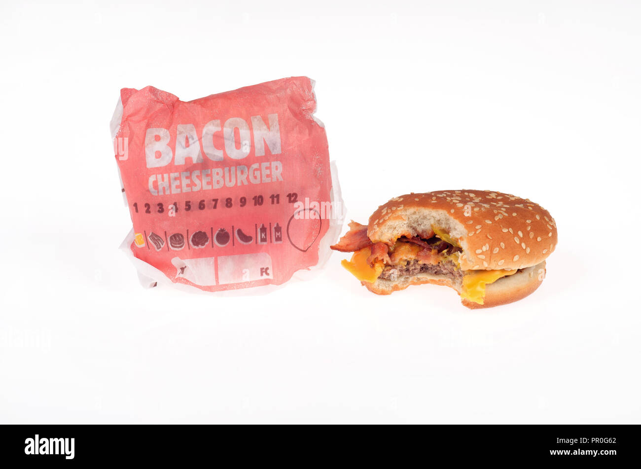 2 Burger King bacon cheeseburgers, one with a bite taken out and one in wrapper - Stock Image