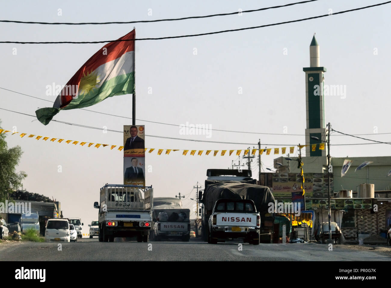 Kurdistan flag, mosque, street scene in the Nineve plain, Northern Iraq, Kurdistan - Stock Image