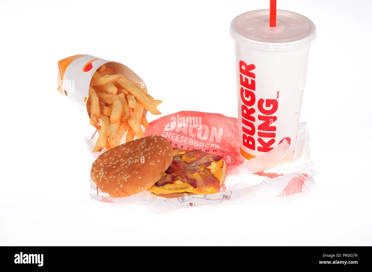 Burger meal with bacon cheeseburger, french fries or chips and a soda on white background - Stock Image
