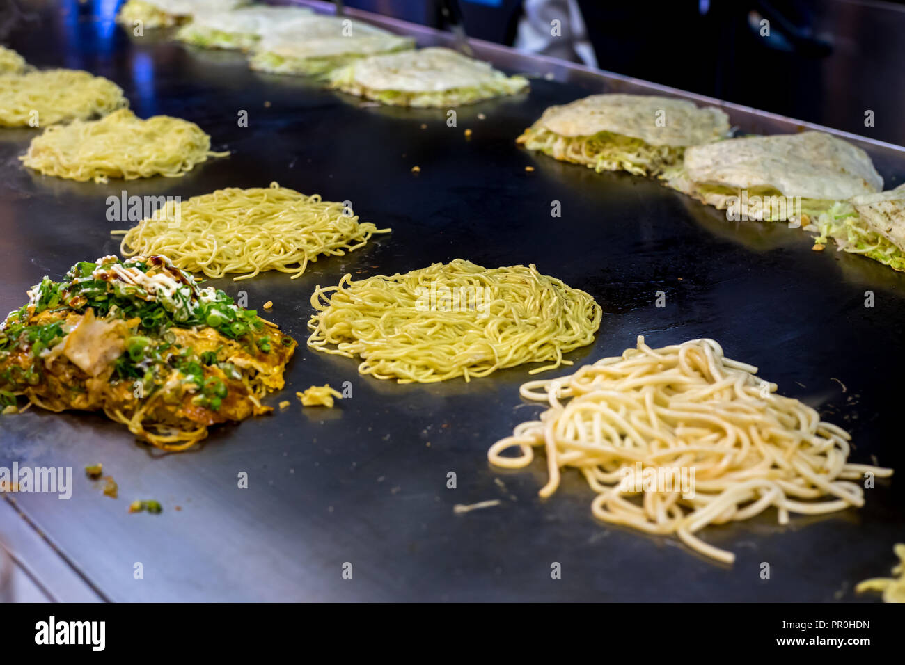 Okonomiyaki being prepared on a large griddle, Hiroshima, Japan, Asia Stock Photo
