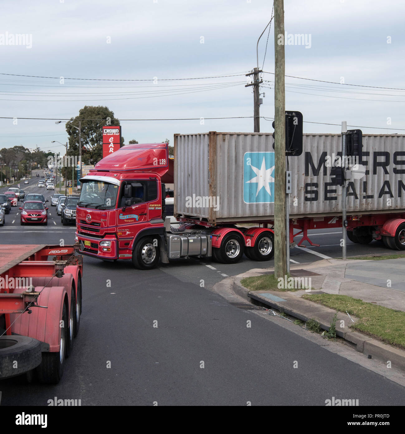 A large semi trailer truck carrying a Maersk Sealand shipping container turning a corner in Sydney traffic, Australia - Stock Image